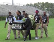 Football players honor fallen teammate by carrying coffin across field